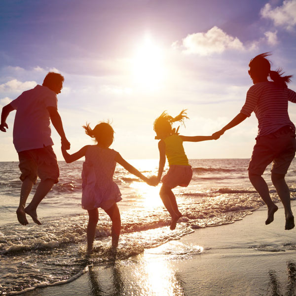 family jumping in air during sunset on the beach